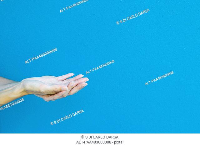 Cupped hands in front of blue wall, cropped view