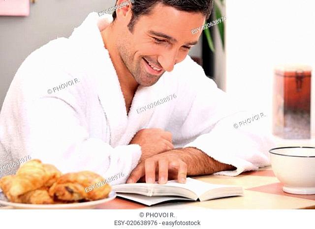 man reading a bookat breakfast