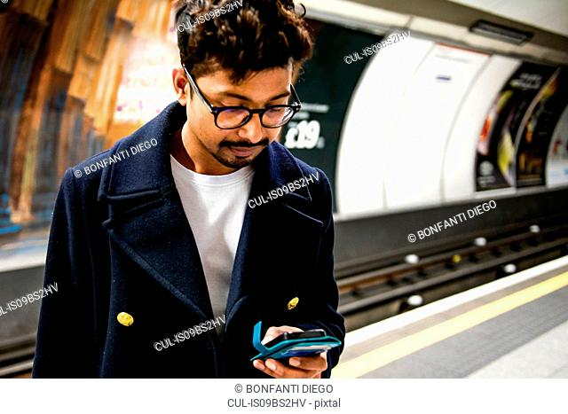 Businessman using smartphone on platform of subway station, London, UK