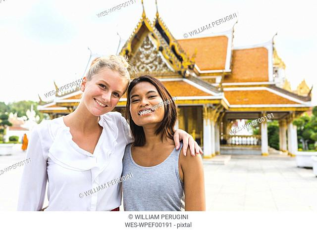 Thailand, Bangkok, portrait of two smiling friends in front of temple