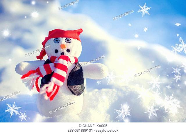 Winter concept with snowman rock style on snow background. Dressed with red and white striped scarf, red bandana and leather sleeveless in the snow outside