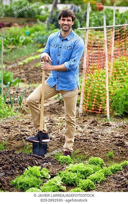 Farmer looking at camera with confidence, digging shovel, Urban vegetable garden, Urban orchards, Ekogunea, Donostia, San Sebastian, Gipuzkoa, Basque Country