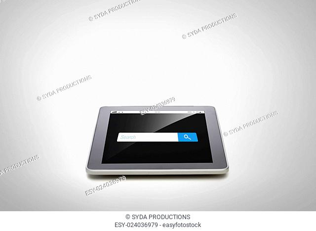 business, technology, internet and modern gadget concept - close up of tablet pc computer with browser search bar on screen gray background