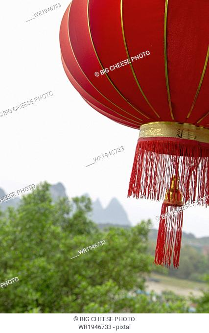 Red lantern hanging in front of a view of the Karst mountains, Yangshuo, China