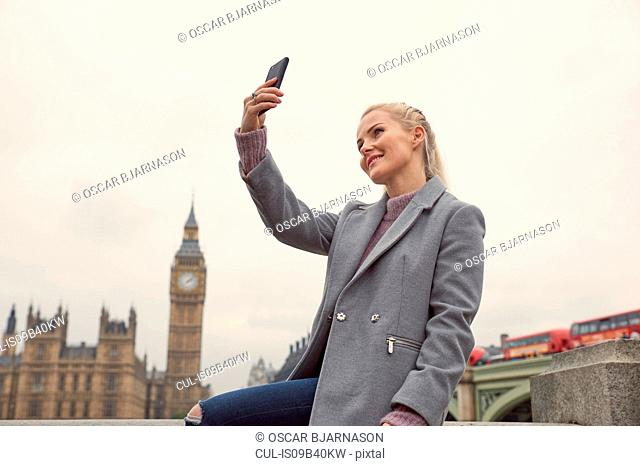 Mid adult woman taking selfie, using smartphone, Houses of Parliament in background, London, England