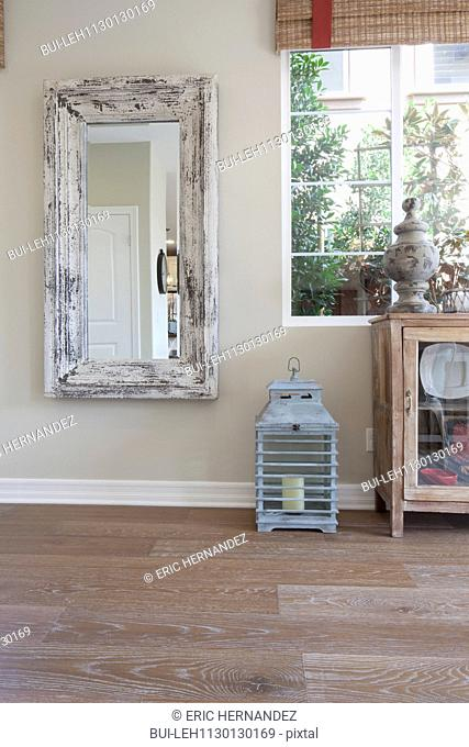 Rectangle shaped mirror and lantern by window in house
