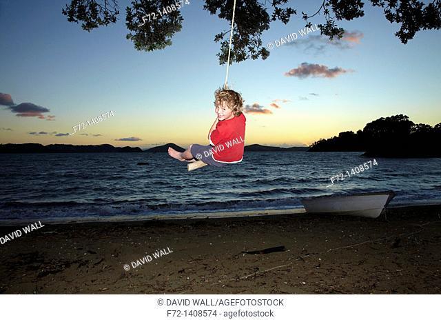 A young boy on a rope swing at dusk under a Pohutukawa tree at Oamaru Bay, Coromandel Peninsula, North Island, New Zealand