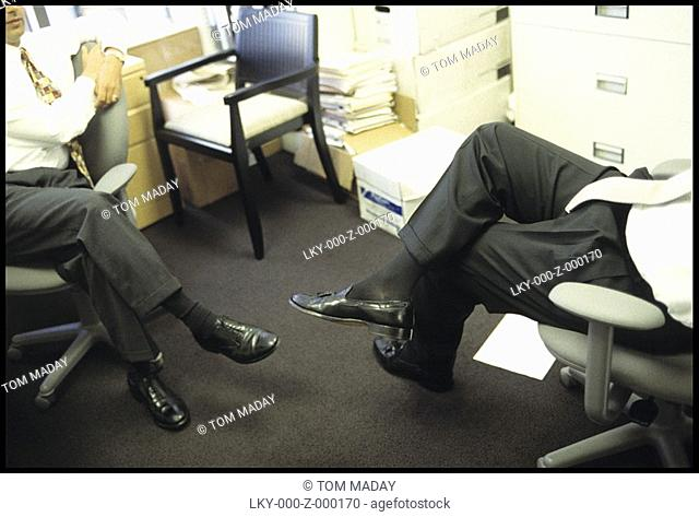 Cropped image of two men having a conversation in business office