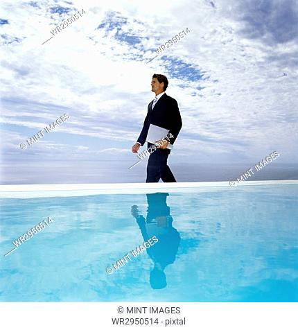 A man in a suit walking along a swimming pool, carrying a laptop