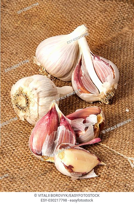 Garlic wholly and cloves scattered on sackcloth