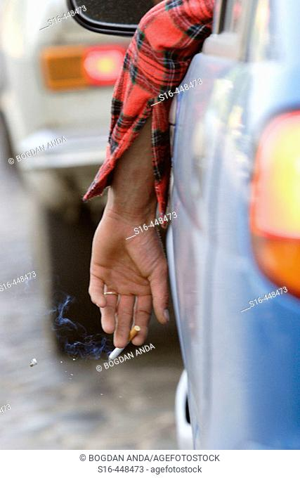 A driver shakes the ashes of his lit cigarette while waiting cought in a traffic jam in downtown Bucharest, Magheru Boulevard - Romania