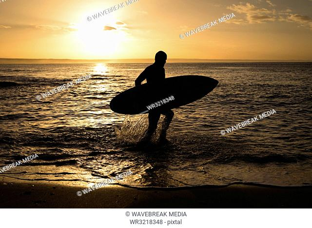 Surfer with surfboard walking on beach