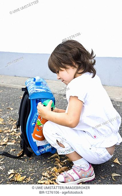 Young schoolgirl sitting in front of her satchel, holding a drinking bottle