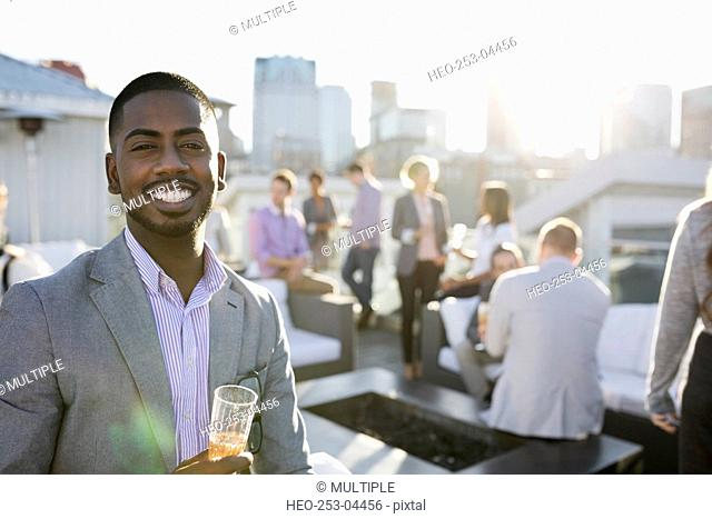 Portrait smiling businessman drinking champagne on urban rooftop