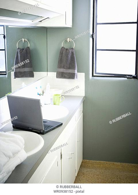 Female in bathroom with laptop and toothbrush