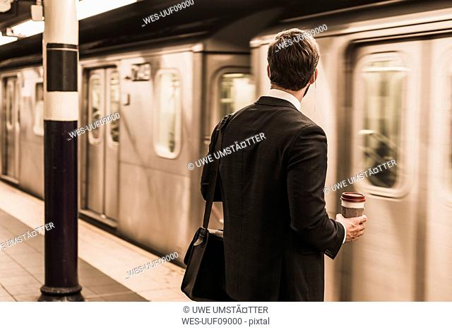 Young businessman waiting at metro station platform, holding disposable cup