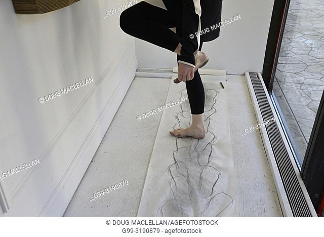 A woman artist standing on paper grabs her foot at the end of a performance, Windsor, Canada