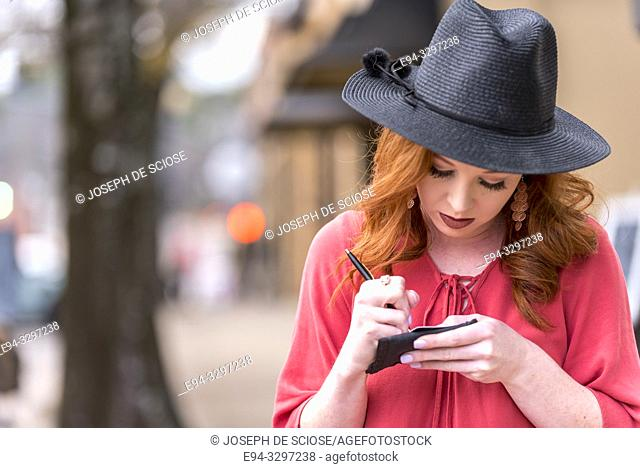Portrait of a 25 year old redheaded woman wearing a black hat in an urban setting