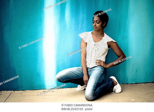 Pensive African American woman kneeling near blue wall