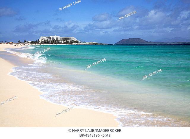 Sandy beach and turquoise sea, Playa Bajo Negro, behind Riu Hotel and Los Lobos Island, Corralejo Natural Park, Fuerteventrura, Canary Islands, Spain