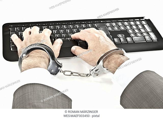 Close up of businessman's hand cuffed while cyber crime