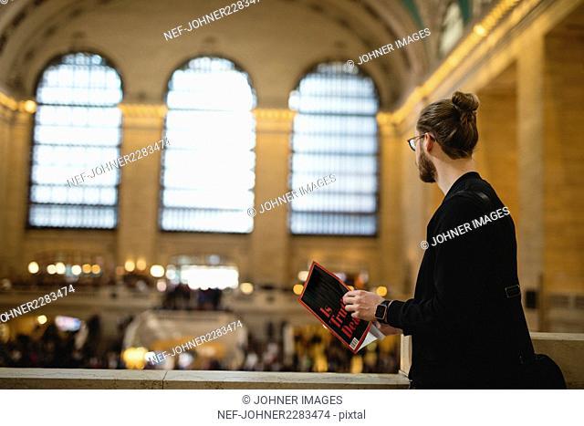 Man holding newspaper, looking away