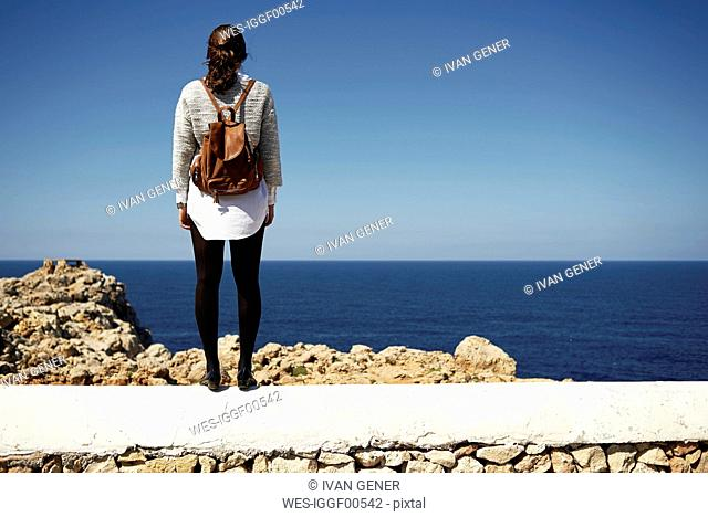 Young brunette woman standing on wall, looking at view