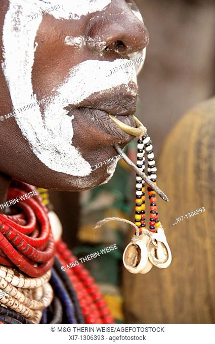 Detail of a Karo woman's face with tongue piercing and a nail in the lip, Omo river valley, Southern Ethiopia