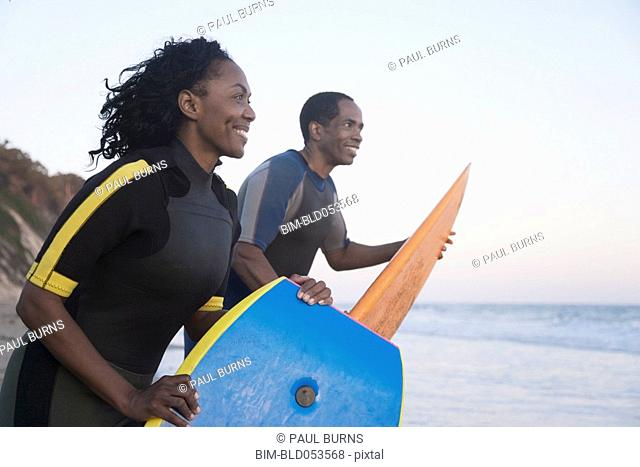 African couple carrying surfboard and boogie board