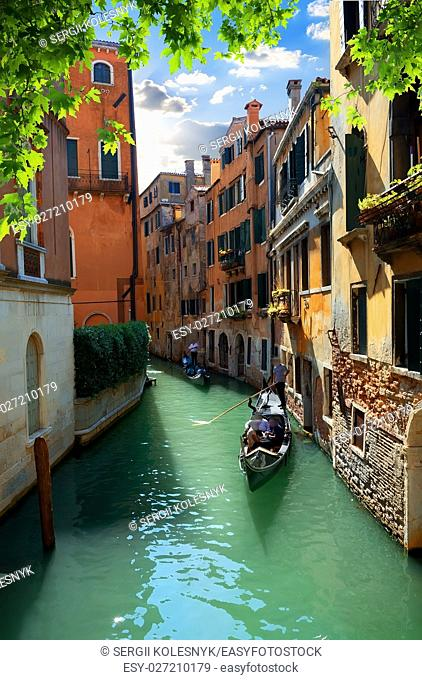 Gondola ride in venetian streets at summer day, Italy