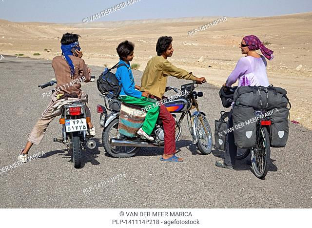 Young Iranian men on motorcycles talking to a female Western touring cyclist in Iran, close to the border with Turkmenistan in the Karakum desert