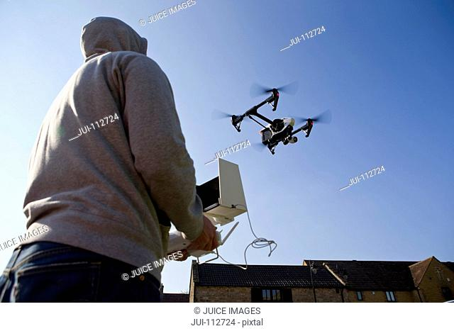 Hooded man operating surveillance drone in blue sky
