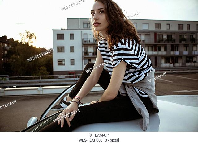 Serious young woman sitting on car roof