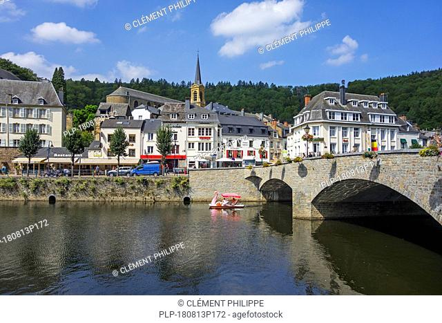 Paddle boat with tourists passing under the bridge Pont de Liège in the city Bouillon in summer, Luxembourg Province, Belgian Ardennes, Belgium