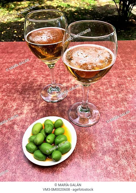 Two glasses of beer with green olives in a terrace