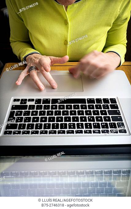 View of woman's hands with ring and laptop computer