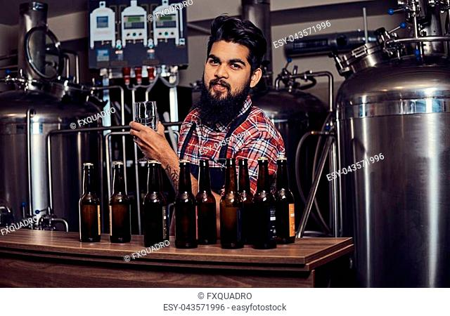 Stylish full bearded Indian man in a fleece shirt and apron holds a glass of beer, standing behind the counter in a brewery