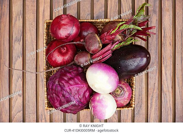 Basket filled with root vegetables all red, red onion, beetroot, aubergine, red cabbage, turnip