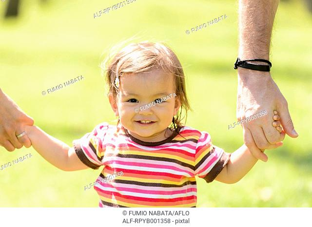 Toddler holding parents hands in a park