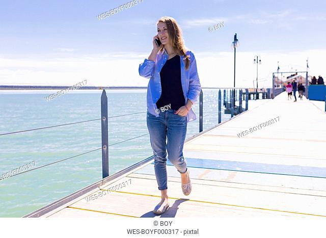Italy, Lignano Sabbiadoro, woman with smartphone at the seaside