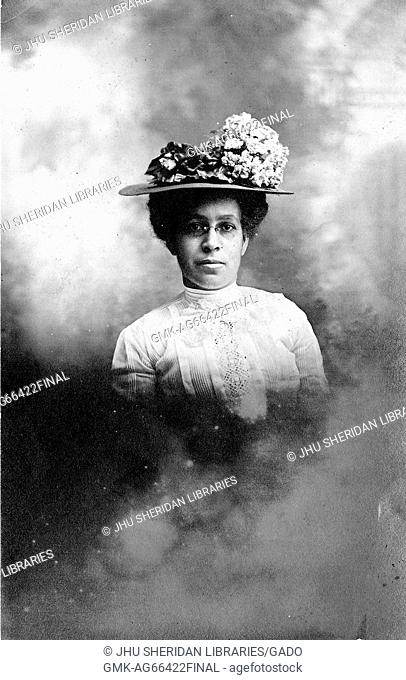 African-American woman, waist up portrait with a serious facial expression, wearing ornate hat with flowers, white dress and glasses, 1915