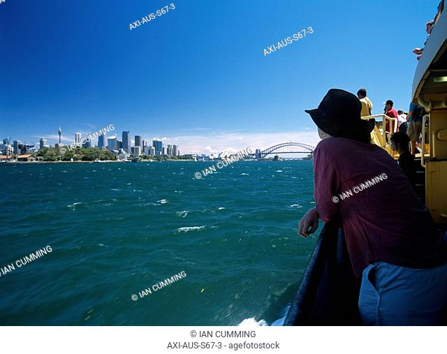 Woman leaning on railing on a ferry passing Sydney city centre