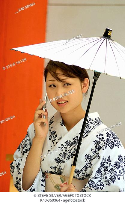 Woman in traditional costume talking on mobile phone at Hanagasa Junko (procession of floral bonnets) during Gion Matsuri traditional Japanese festival