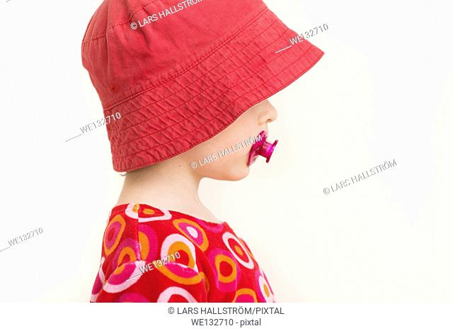 Profile portrait of little girl with red hat and pacifier