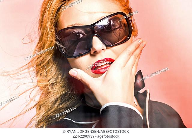Attractive surprised young woman wearing mens fashion sunglasses with surprised expression on red background. Beauty and fashion concept