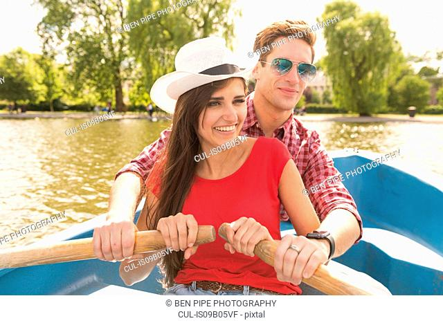Happy young couple rowing a boat together in Regents Park, London, UK