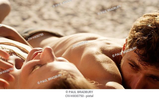 Young couple sunbathing on sunny beach