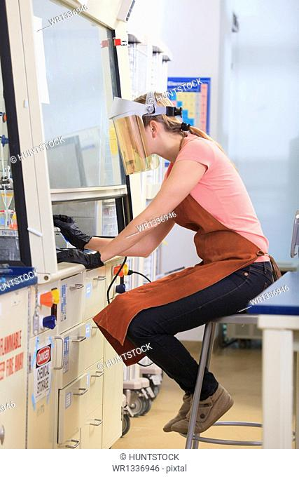 Engineering student wearing protective equipment while working on chemistry experiment in fume hood