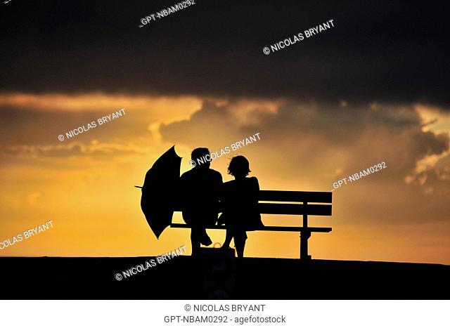 COUPLE ON A BENCH UNDER A STORMY SKY AT SUNSET, CAYEUX-SUR-MER, BAY OF SOMME, SOMME 80, FRANCE