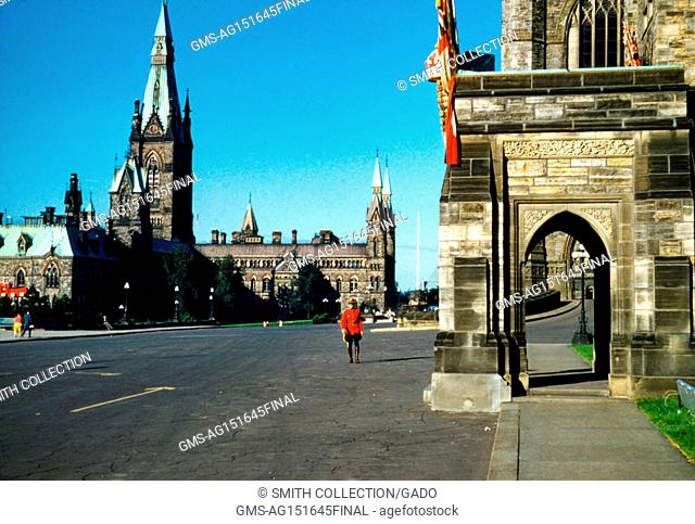 A member of the Royal Canadian Mounted Police, known coloquially as a Mountie, walks among ornate buildings near the Canadian Parliament, Ottawa, Ontario
